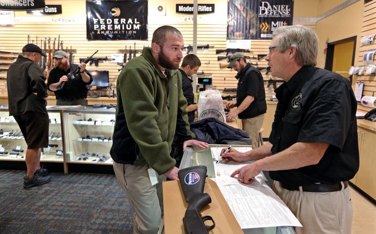 Customer David Schwartz of Goochland County completed the purchase of a shotgun Tuesday at Colonial Shooting Academy in Henrico County. Assistant retail manager Peter Schreiber went over paperwork with him. Photo credit: P. KEVIN MORLEY/TIMES-DISPATCH